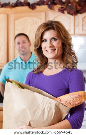 A beautiful woman carrying a grocery bag with her husband watching in the background - stock photo