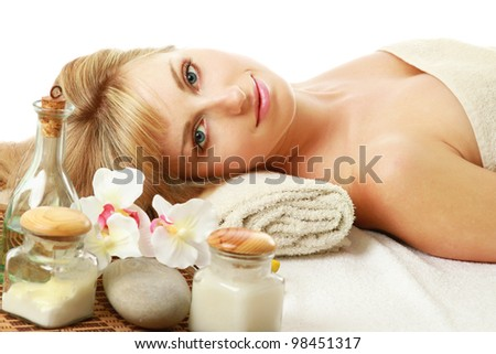 A beautiful woman enjoying spa treatment is lying on a towel over white - stock photo