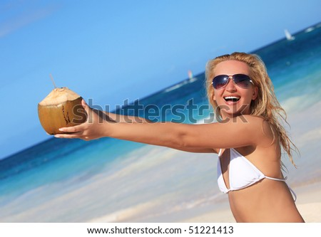 A beautiful woman enjoying sunny day on the beach and  holding coconut in her hands - stock photo