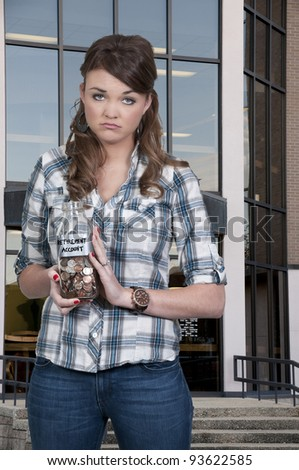 A beautiful woman holding her retirement account of coins in a milk bottle - stock photo