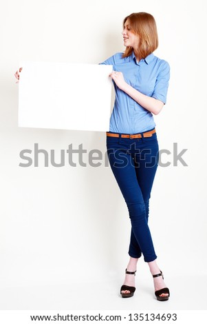 A beautiful woman holds out a big blank card Isolated on white background - stock photo