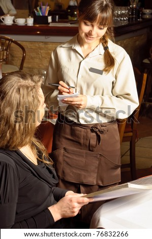 A beautiful woman in restaurant. Waiter is taking the order - stock photo