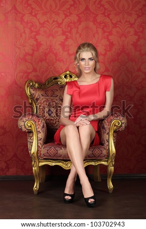 A beautiful woman is sitting in a antique chair against the red wall - stock photo