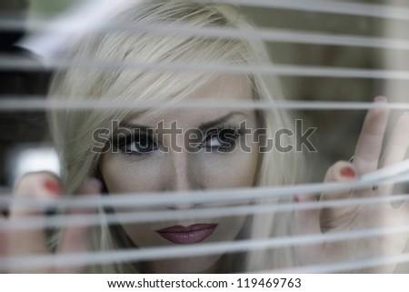A beautiful woman looks through the window cornices - stock photo