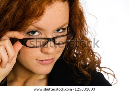A beautiful woman peering over her glasses in a seductive manner. - stock photo