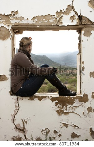 A Beautiful woman sitting and staring out of a window frame of old building - stock photo