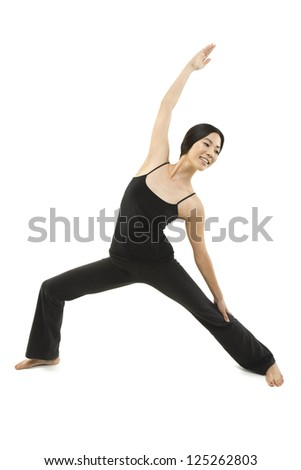 A beautiful woman stretches and does a Yoga pose - stock photo