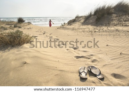A beautiful woman walks barefoot through sand dunes towards to sea leaving her flip flops behind - stock photo