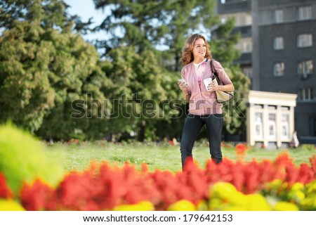 A beautiful woman with a mobile phone and coffee to go walking in a city park. - stock photo