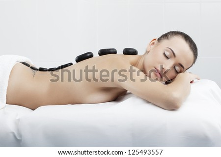 A beautiful woman with perfect skin is spa massage therapy in clinic - stock photo