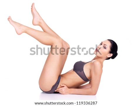 A beautiful woman with raised up long legs isolated on white - stock photo