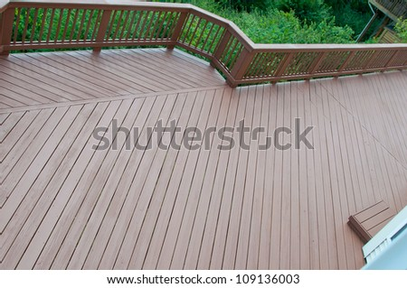 A beautiful wood deck after application of fresh paint and stain. - stock photo
