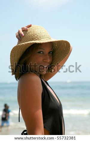 a beautiful young african american woman enjoys a day at the beach - stock photo