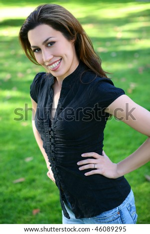 A beautiful young and happy hispanic woman in the park - stock photo