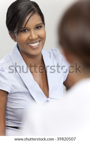 A beautiful young Asian businesswoman with a wonderful smile in a meeting with her colleague out of focus in front of her. - stock photo