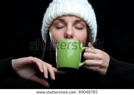 a beautiful young attractive charming girl in a white hat and black gloves with a green mug in hand, on a black background - stock photo