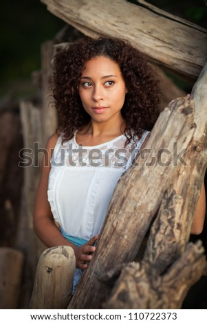 A beautiful, young black woman poses  by driftwood. - stock photo