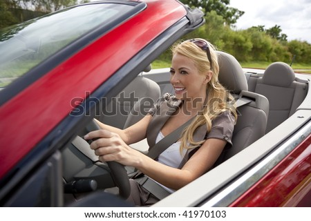 A beautiful young blond woman driving her convertible car in the sunshine. - stock photo
