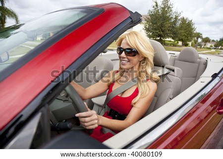 A beautiful young blond woman driving her convertible car wearing a red dress and sunglasses - stock photo