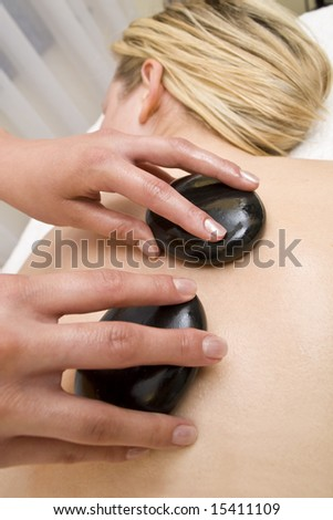 A beautiful young blond woman receives a hot stone massage from a beautician - stock photo