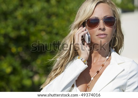 A beautiful young blond woman wearing aviator sunglasses and a white suit talking on her cell phone in a sunny location - stock photo