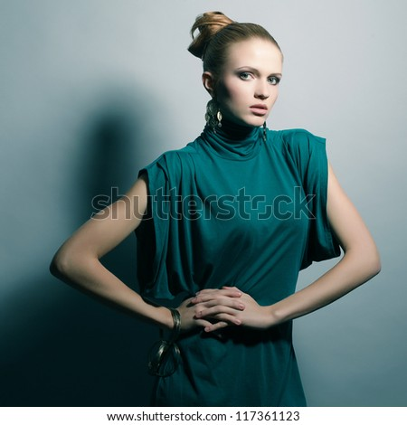 a beautiful young blonde in a green (blue) dress wearing wristbands over light blue background. studio shot - stock photo