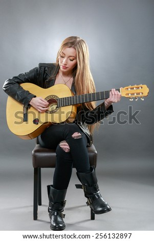 a beautiful young blonde with a classical guitar - stock photo