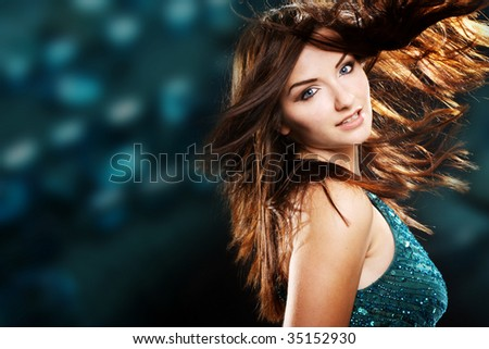 A beautiful young brunette woman dancing with her hair in motion in a nightclub scene. - stock photo