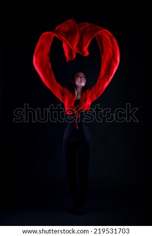 A beautiful young Chinese girl performs a traditional Chinese dance with long red sleeves, a red heart on a black background  - stock photo