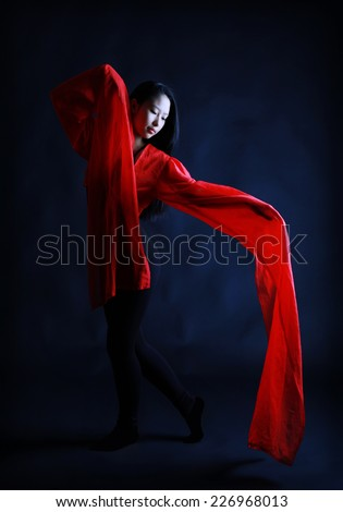 A beautiful young Chinese girl performs a traditional Chinese dance with long red sleeves, a red heart on a dark background, Contrast  - stock photo