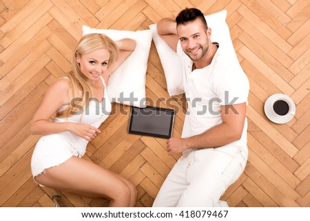 A beautiful young couple on the floor in their new home with a Tablet PC.