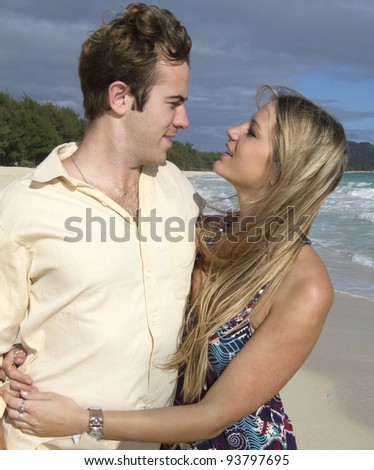 A beautiful young couple stare into each other's eyes on the beach in Hawaii - stock photo