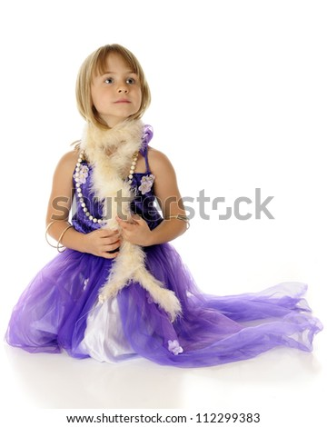 A beautiful young elementary girl playing dress-up in a fancy purple dress, necklace, bracelets and a boa.  On a white background. - stock photo