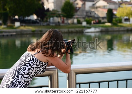 A beautiful young female photographer leaning over the bridge railing to take a photo of river and the town view - stock photo