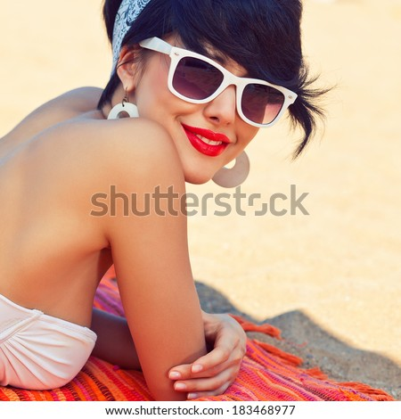 a beautiful young girl in retro look with red lips in a white swimsuit, a bandana and sunglasses is lying on the beach in the shade and looking into the camera - stock photo