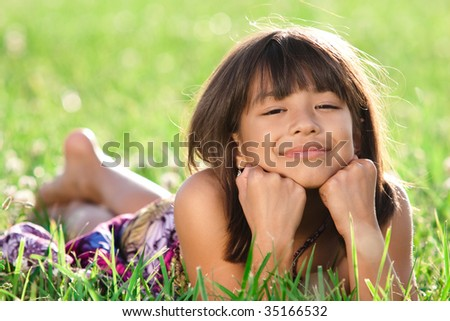 a beautiful young girl lays in a field smiling at the camera - stock photo