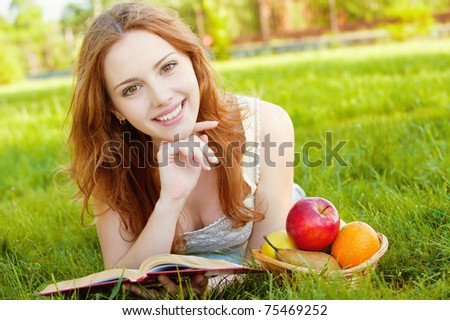 A beautiful young girl lying on the grass and reading a book beside a basket of fruit is, on a background of green nature - stock photo