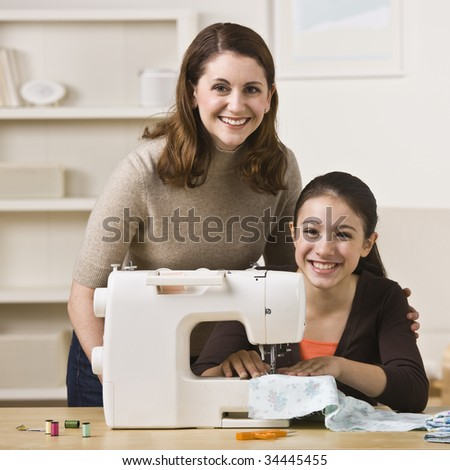 A beautiful young girl sewing with her mother.  They are smiling at the camera.  Square framed shot. - stock photo