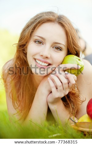 A beautiful young girl with an apple lying on the grass on a background of green nature - stock photo