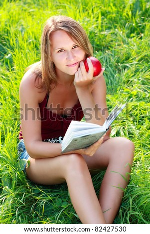 A beautiful young girl with an apple sitting on the grass and reading a book on a background of green nature - stock photo