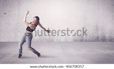 A beautiful young hip hop dancer dancing contemporary urban street dance in empty clear grey wall background concept. - stock photo