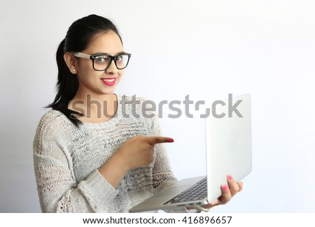 A Beautiful young Indian woman  pointing at laptop screen against white background. - stock photo