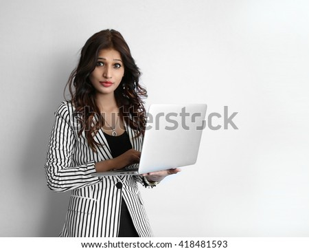 A Beautiful young Indian woman working on laptop against a white background - stock photo