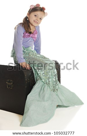 A beautiful young mermaid happily sitting on an old treasure chest.  On a white background. - stock photo