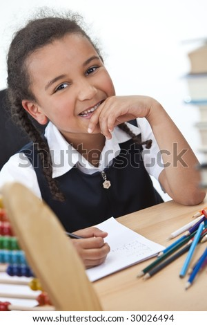 A beautiful young mixed race girl writing in a school classroom surrounded by books and an abacus - stock photo