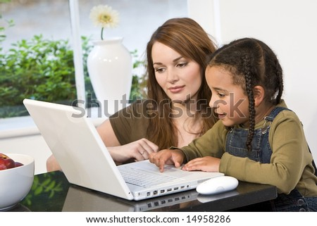 A beautiful young mother and her mixed race young daughter using a laptop at home in the kitchen. - stock photo