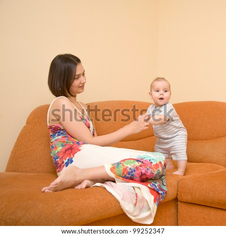 A beautiful young mother wearing a dress with flowers and a charming kid on the orange sofa. Baby learning to stand - stock photo