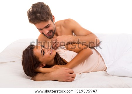 A beautiful young passionate couple in bed - stock photo