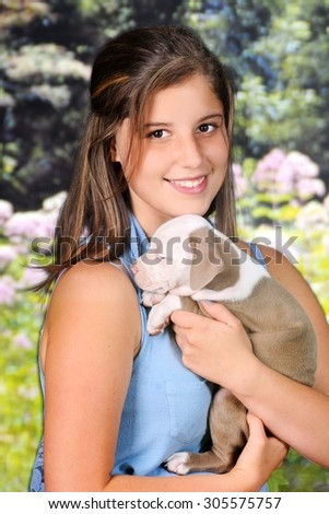 A beautiful young teen happily holding her baby pit bull.   - stock photo