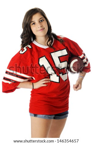 A beautiful young teen holding a football in an over sized red jersey and shorts.  On a white background. - stock photo